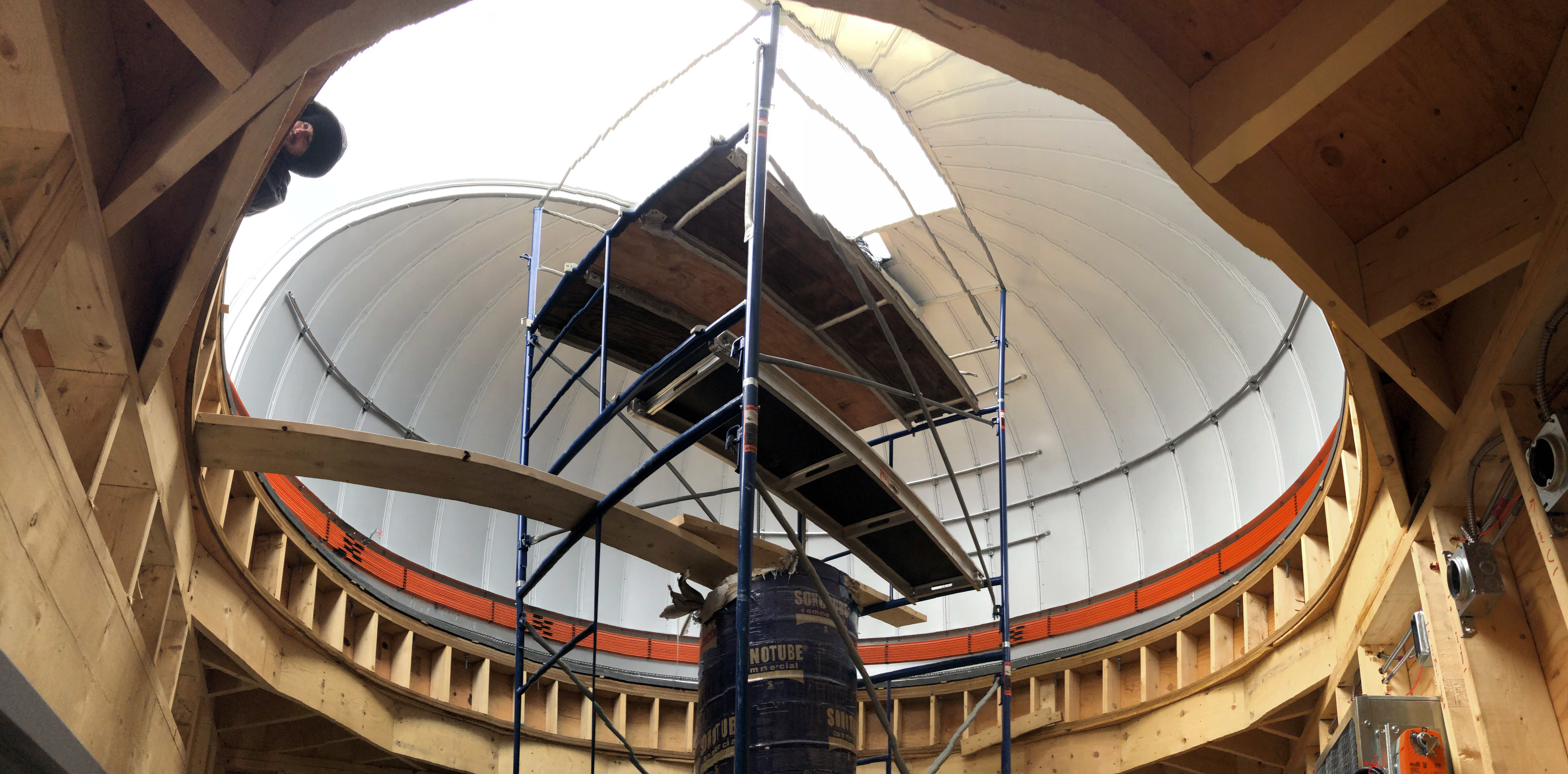 A wide-field image of the dome interior. Note that edges are a little warped in this image due to the camera's odd stitching of the frames. You can see the top of the pier and the orange power line system for dome operations which make the system effectively wireless. No wires will be dangling down from above to control the dome's motion.